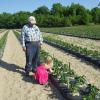 Dave and his granddaughter in the pepper field.  She's checking her new crop.